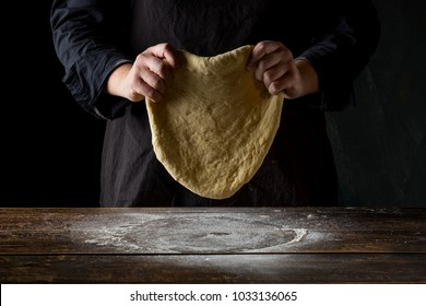 Chef hands preparing dough for italian pizza, pasta or bread preparation over wooden background, top view, flat lay