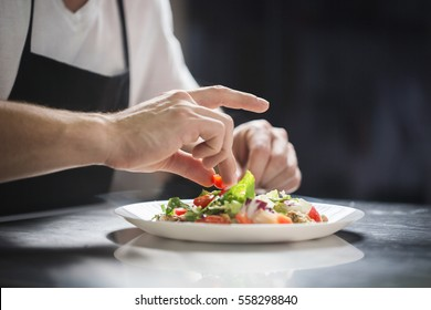 Chef hands preparing vegetable salad