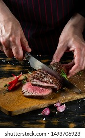 Chef hands slicing beef steak with knife on wood cutting desk. Top view food preparation process concept.