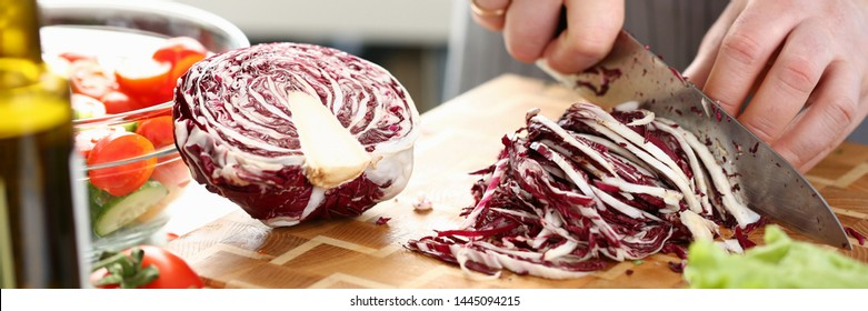 Chef Hands Slicing Purple Salad Cabbage Halve. Male Chopping Red Cole on Cutting Board in Kitchen at Home. Healthy Grocery Culinary Recipe. Fresh Dieting Ingredient Horizontal Photography