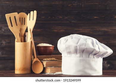 Chef hat with books, bowl of flour and kitchen utensils on wooden background