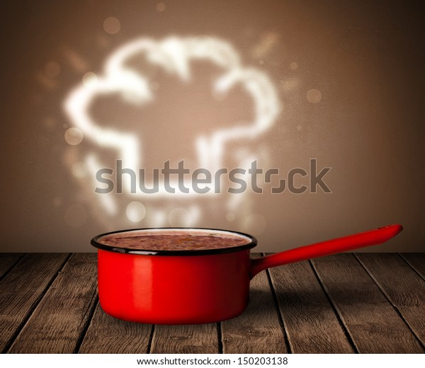 Chef hat coming out from cooking pot on wooden table