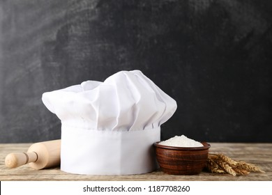 Chef hat with flour and rolling pin on wooden table