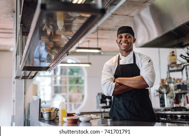 Chef with his arms crossed standing at restaurant kitchen. Male cook wearing apron standing by kitchen counter and smiling.