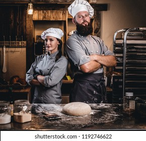 Chef with his assistant in cook uniform posing with crossed arms near table with ready dough in the bakery.