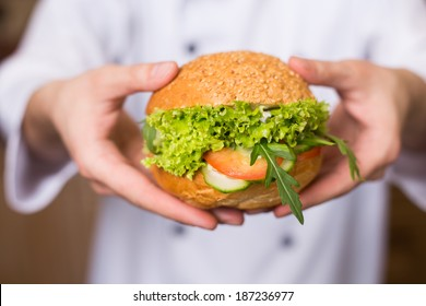 Chef holding a big sandwich with lettuce, tomatoes and cucumber on the kitchen