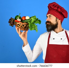 Chef holding a bowl full of raw fresh organic vegetables on blue background, promoting eating seasonally and sourcing from local producers. Cooking healthy and fresh concept