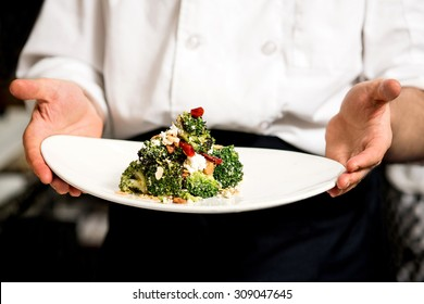 Chef holding broccoli salad, ready to serve