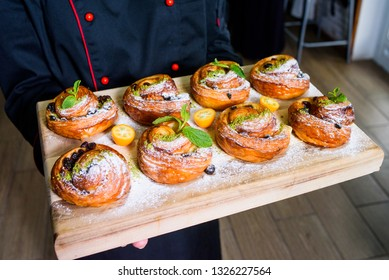 chef holding fresh homemade bakery with berries and topping