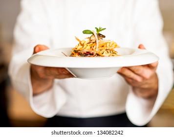 Küchenchef, der Pasta-Salat bewässert und serviert.