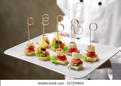 Chef holding plate with assorted canapes closeup