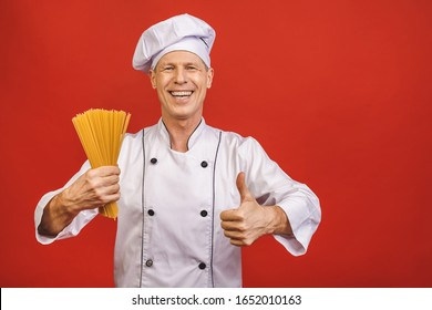Chef holds bunch of spaghetti in hand. Catering and italian food concept isolated on red background. Cook with satisfied face in white uniform holds dry pasta showing thumbs up.