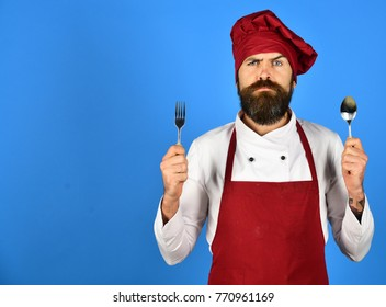 Chef holds cutlery. Cook with serious face in burgundy hat and apron holds spoon and fork. Man with beard holds kitchenware on blue background, copy space. Cooking process commercial concept.