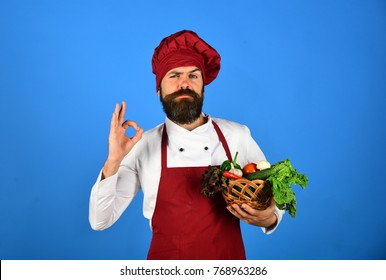Chef holds lettuce, tomato, pepper and mushrooms. Cook with confident face in burgundy uniform hold vegetables in bowl showing ok sign. Vegetarian restaurant concept. Man with beard on blue background