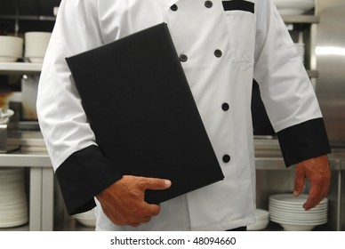 A chef holds a menu in a restaurant kitchen