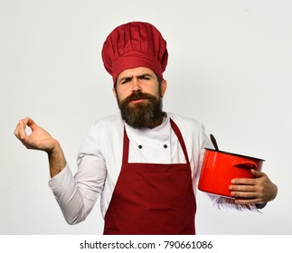 Chef holds soup or compote making italian gestures. Cook with funny grimace in burgundy uniform has casserole with ladle. Man with beard holds red pot on white background. Professional cookery concept