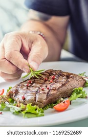 Chef in hotel or restaurant kitchen cooking only hands. Prepared beef flank steak with vegetable decoration.