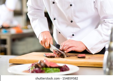 Chef in hotel or restaurant kitchen cooking, only hands, he is cutting meat or steak for a dish on plate