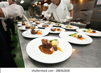 Chef in hotel or restaurant kitchen cooking for dinner