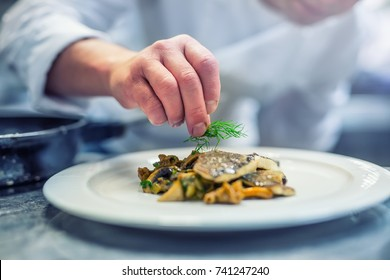 Chef in hotel or restaurant kitchen cooking, only hands. Prepared fish steak with dill decoration.
