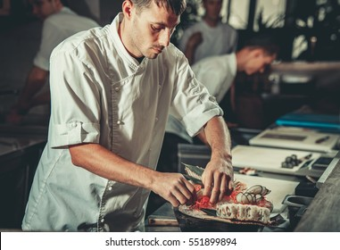 Chef in hotel or restaurant kitchen decorating dish. He is working on maki rolls. Preparing sushi set