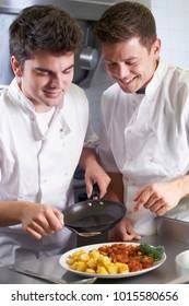 Chef Instructing Male Trainee In Restaurant Kitchen