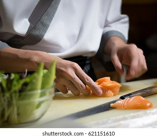 Chef Japanese cuisine in hotel or restaurant kitchen cooking, only hands. He is working sushi