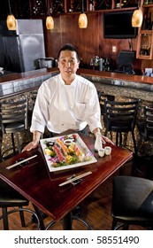 Chef in Japanese restaurant with sushi platter