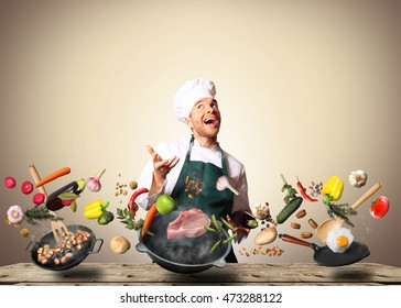 Chef juggling with vegetables and other food in the kitchen