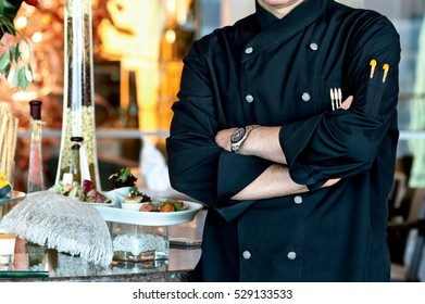 The chef in the kitchen, the black uniform and the chief posture.