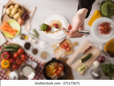 Chef in the kitchen holding a fork with spaghetti, tomato sauce and basil, food ingredients and utensils on background, top view