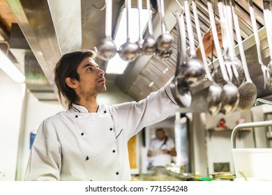 Chef in the kitchen taking a ladle spoon. Young cook wearing a white apron and choosing a soup spoon. Food and work concepts