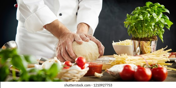 Chef kneading raw dough for an Italian pizza in a close up view of his hands and assorted fresh ingredients