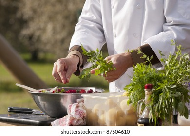 Chef makes beetroot salad with organic parsley. Outdoors.