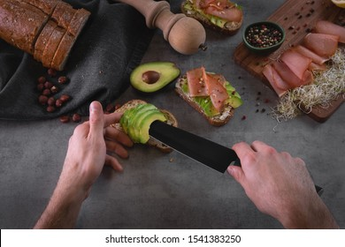Chef making avocado sandwiches with bread, nuts, ham, sprouts and goat cheese on grey stone slate background. Man making breakfast in the kitchen. Healthy food preparation. Toned faded background