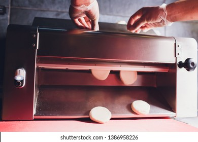 Chef making dough pastry sheeter bakery Baker forming shaping dough rolled pastry metal work table closeup hands process of preparing bread khinkali dough roller machine thin pasta sheet Top view.