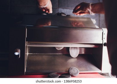 Chef making dough pastry sheeter bakery Baker forming shaping dough rolled pastry metal work table closeup hands process of preparing bread khinkali dough roller machine thin pasta sheet Top view