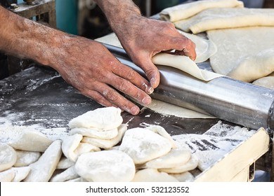 Chef making dough pastry sheeter at bakery Baker forming shaping dough rolled pastry metal work table closeup hands process of preparing bread khinkali dough roller machine thin pasta sheet Top view