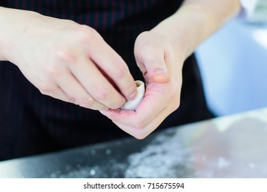chef making dumpling, A cook is making dumplings with his hands. Close-up of chef's hands filling