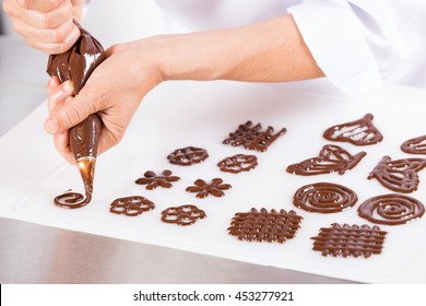 Chef making figures with chocolate to decorate a cake