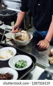 Chef making Hakata style Chashu Ramen by holding ramen noodle in Shio soup with chopsticks.