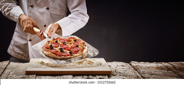 Chef making a homemade pepperoni pizza in an Italian pizzeria lifting it onto a wooden board from the fire with a metal paddle in a rustic panorama banner with copy space