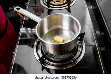 chef making melt butter in pot