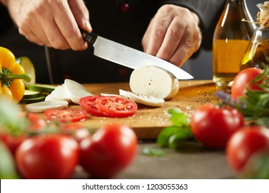 Chef making traditional Italian Caprese salad slicing mozzarella cheese with a large knife with tomatoes and basil in the foreground