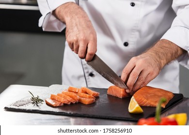 Chef male cutting fish fillet. Closeup chef hands slice salmon at kitchen table. Cook in uniform cutting red fish at professional kitchen.