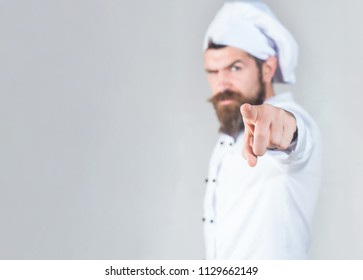 Chef man. Confident male chef with beard, mustache shows finger on you. Cook points forward. Chef in uniform pointing at you. Chef, cook, baker pointing to front. Selective focus on hand. Copy space.