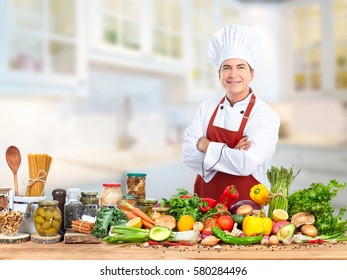 Chef man in kitchen over food vegetables background.
