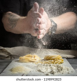 chef men hands with flour splash over the table. preparation of fresh homemade pasta on a black background