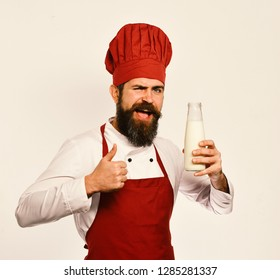 Chef with milkshake or yoghurt shows thumbs up. Man with beard holds bottle of milk on white background. Organic ingredients concept. Cook with flirty face in burgundy uniform has liter of fresh milk