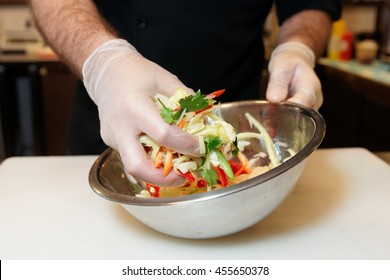 Chef is mixing a vegetarian salad in stainless steel bowl